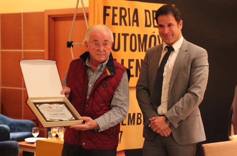 Enrique Tomás recibe de Raúl Palacios una placa de homenaje.