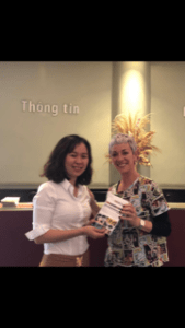 Carol Gil haciendo entrega de uno de los ejemplares de Cada mirada es única en Vietnam.