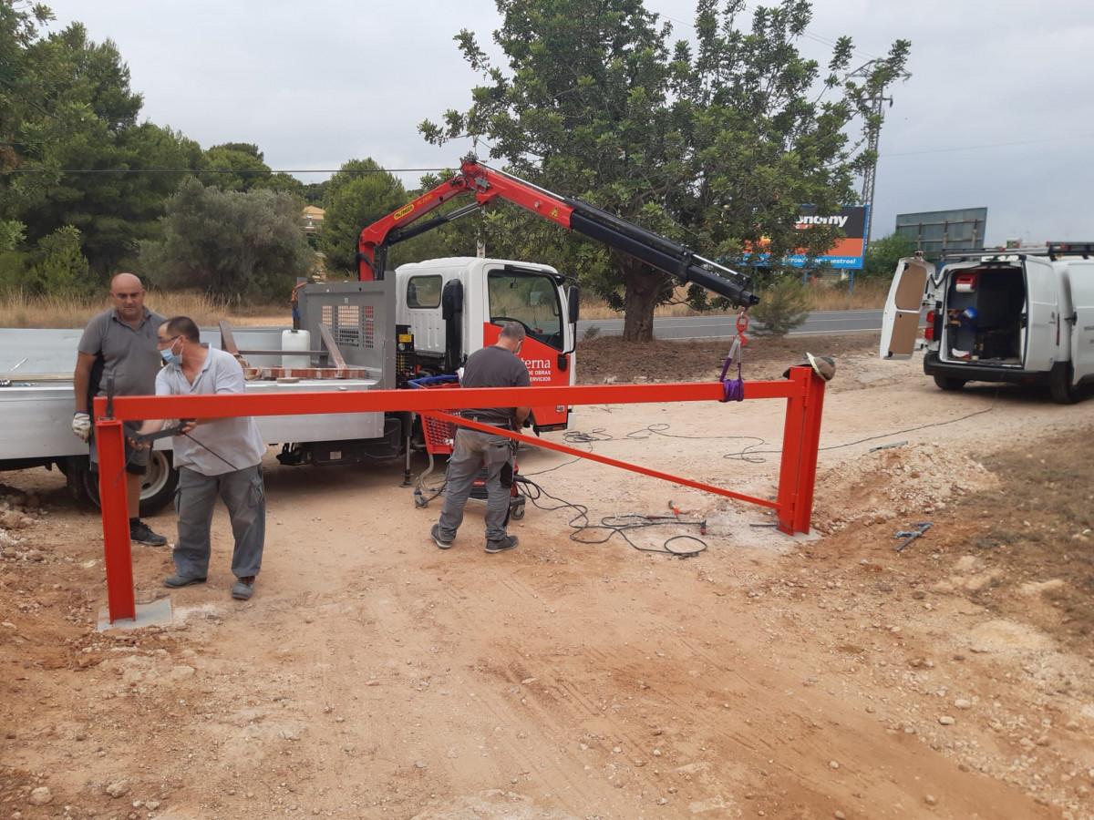 Operarios del Ayuntamiento de Paterna instalan una barrera en un camino del término municipal para impedir vertidos.